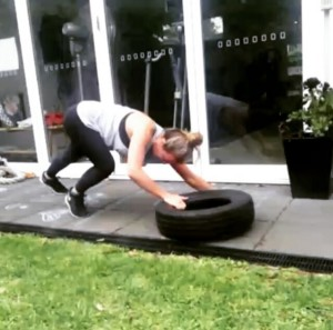 Tyre single arm drag (plank position). Walk along on your hands and toes, dragging the tyre with you, or pushing it out in front.